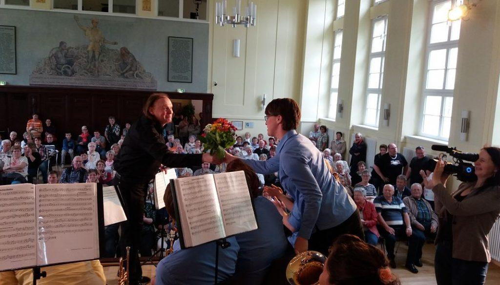 Stadtmusikdirektor überreicht Blumenstrauß an Muttis im Orchester. Foto: JBO