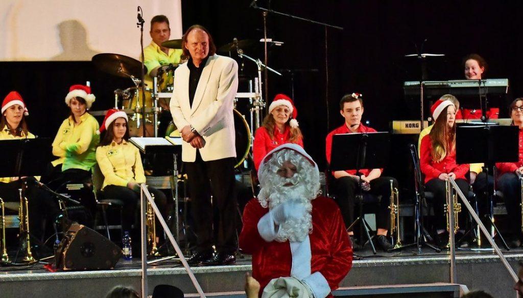 Passend zu weihnachtlichen Melodien des Jugendblasorchesters verteilte der Weihnachtmann kleine Geschenke im Publikum. Foto: Thomas Kube